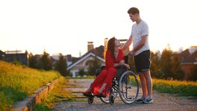 Mädchen in einer Rollstuhl-netten Unterhaltung mit ihrem jungen Mann auf dem Hintergrund des Hauses, des grünen Grases und der Bä stock video
