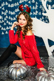Mädchen in einer roten Strickjacke, die mit Weihnachtsgeschenken sitzt Betrug des neuen Jahres Stockfotos