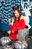 Mädchen in einer roten Strickjacke, die mit Weihnachtsgeschenken sitzt Betrug des neuen Jahres Stockfotografie