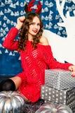 Mädchen in einer roten Strickjacke, die mit Weihnachtsgeschenken sitzt Betrug des neuen Jahres Lizenzfreies Stockbild