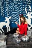 Mädchen in einer roten Strickjacke, die mit Weihnachtsgeschenken sitzt Betrug des neuen Jahres Stockbilder