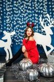 Mädchen in einer roten Strickjacke, die mit Weihnachtsgeschenken sitzt Betrug des neuen Jahres Lizenzfreie Stockbilder