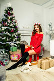 Mädchen in einer roten Strickjacke sitzt auf einem Spielzeugelch nahe einem Weihnachtsbaum Lizenzfreie Stockbilder