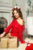 Mädchen in einer roten Strickjacke sitzt mit einem Geschenk Weihnachten und neues Jahr c Stockfotografie