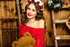 Mädchen in einer roten Strickjacke sitzt mit einem Teddybären Weihnachten und neues Stockbild
