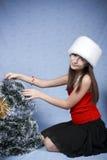 Mädchen in einer Schutzkappe mit den Weihnachtsdekorationen. Stockfotografie