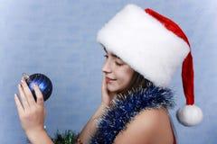 Mädchen in einer Schutzkappe mit den Weihnachtsdekorationen. Lizenzfreie Stockbilder