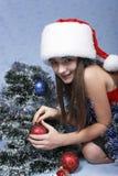 Mädchen in einer Schutzkappe mit den Weihnachtsdekorationen. Stockbild