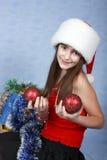 Mädchen in einer Schutzkappe mit den Weihnachtsdekorationen. Lizenzfreies Stockbild