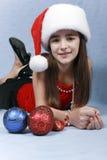 Mädchen in einer Schutzkappe mit den Weihnachtsdekorationen. Stockfotos