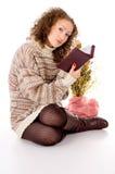 Mädchen in einer Strickjacke und in einem Buch Lizenzfreie Stockfotografie