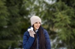 Mädchen in einer Strickmütze und in den Handschuhen hält einen Schnee in Form eines h lizenzfreies stockfoto