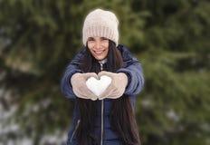 Mädchen in einer Strickmütze und in den Handschuhen hält einen Schnee in Form eines h stockfotografie
