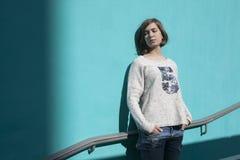 Mädchen in einer weißen Strickjacke schließt träumerisch ihre Augen vom hellen Sonnenschein gegenüber von der blauen Wand in der  Stockfotografie