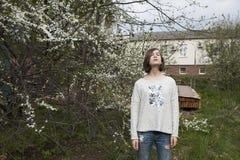 Mädchen in einer weißen Strickjacke schließt träumerisch ihre Augen vom hellen Sonnenschein im Garten nahe der blühenden Kirsche Stockbild