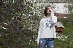Mädchen in einer weißen Strickjacke schließt träumerisch ihre Augen vom hellen Sonnenschein im Garten nahe der blühenden Kirsche stockfotografie