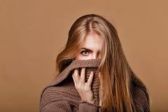 Mädchen eingewickelt in einer warmen Strickjacke Wir sehen nur die Augen Lizenzfreie Stockfotografie