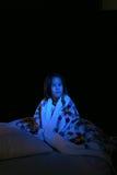 Mädchen eingewickelt oben in der Steppdecke in der Dunkelheit Stockfotografie