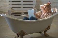 Mädchen entspannen sich in der Badewanne mit Laptop halten Blog Frauenarbeit über Computer im Hauptbad Bewegliches Geschäft und K Lizenzfreie Stockbilder