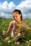 Mädchen erfasst Blumen auf einem Gebiet Stockfotos