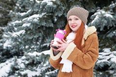 Mädchen erhalten warmer und Getränktee im Winterpark E Stockfotografie