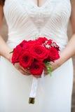 Mädchen in erstaunlichem weißem Hochzeitskleid hält einen hellen roten Blumenstrauß von Rosen Lizenzfreie Stockfotografie
