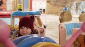Mädchen fährt auf das Karussell und leckt Süßigkeit stock footage