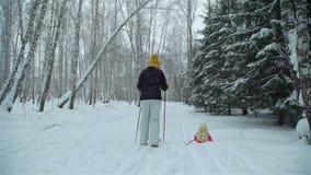 Mädchen fällt in den Schnee beim Ski fahren mit Mutter stock video footage