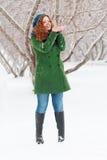 Mädchen fängt Schnee durch die Palmen, die am Wintertag im Freien sind Stockbild