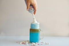 Mädchen fügt Creme in der Schale farbiger blauer Milch hinzu Milchshake, cocktaill, frappuccino Einhornkaffee Stockbild