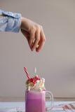 Mädchen fügt Eibisch in der Schale der farbigen Milch mit Sahne und der bunten Dekoration hinzu Lokalisiert auf blauem Hintergrun Stockbild