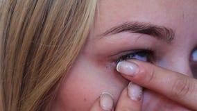 Mädchen fügt eine optische Linse in das Auge ein stock footage