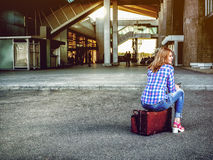 Mädchen am Flughafen sitzt auf einem Koffer, der auf das flache fli wartet Lizenzfreies Stockfoto