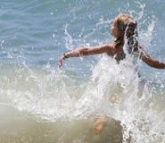 Mädchen-Flugwesen durch Welle stockfoto