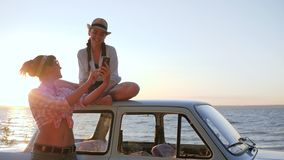 Mädchen fotografieren auf Gerät nahe Fahrzeug auf Seeseite, Freundinnen notieren Video, um auf Backlightinghimmel maschinell zu b stock video