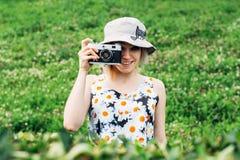 Mädchen fotografierte Retro- Kamera von hinten die Büsche lizenzfreies stockbild