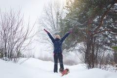 Mädchen freut sich im Winter, ein Mädchen, das in den Winterwald springt stockbild