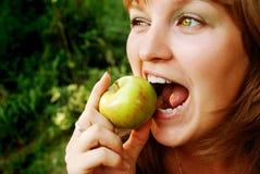 Mädchen gebissener Apfel stockfotografie