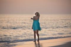 Mädchen geht auf den maledivischen Strand und passt den Sonnenaufgang auf Lizenzfreies Stockfoto