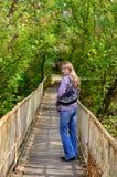Mädchen geht auf eine hölzerne Brücke und dreht sich Stockfotos