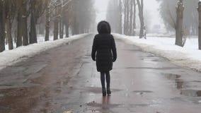 Mädchen geht auf eine nebelige defekte Straße im Winter stock footage