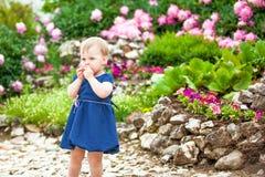 Mädchen geht in den Park mit Blumenbeeten lizenzfreies stockfoto