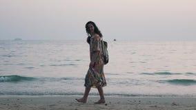 Mädchen geht mit einem Rucksack auf dem Ozean stock video