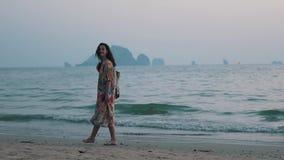 Mädchen geht mit einem Rucksack durch den Ozean stock video