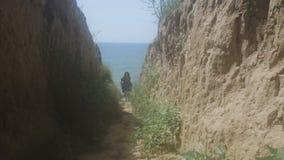 Mädchen geht unten zum Strand auf einem sandigen Ufer stock video