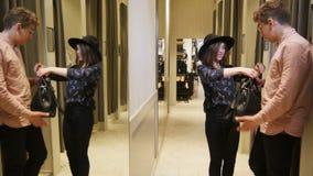 Mädchen geht von der Umkleidekabine mit schwarzer Tasche und Hut heraus stock video footage