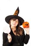 Mädchen gekleidet als Hexe auf einem weißen Hintergrund Lizenzfreie Stockfotos
