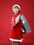 Mädchen gekleidet als Sankt mit einem Beutel des Einkaufens Stockfotos