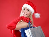 Mädchen gekleidet als Sankt mit einem Beutel des Einkaufens Lizenzfreie Stockfotografie