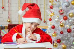 Mädchen gekleidet als Santa Claus-Gedanke über die gewünschten Weihnachtsgeschenke Lizenzfreie Stockfotografie